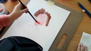 Mão de aluna com pincel a trabalhar no seu retrato