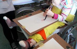 Aluna em cadeira de rodas a pintar com aguarela