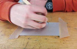 A mão de um aluno a desenhar com a ponta seca o seu desenho na chapa de metal