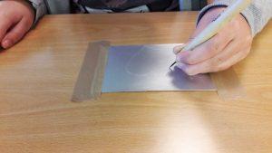 A mão de uma aluna a desenhar com a ponta seca o seu desenho na chapa de metal