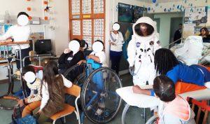 Um grupo de alunos e técnicos olha para a entrada de um astronauta real na sala da escola