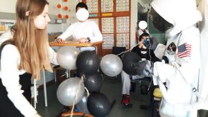 O astronauta e uma técnica assistente do Planetário levam um conjunto de balões cinzentos e pretos, símbolo da Cintura de Asteroides, até um aluno