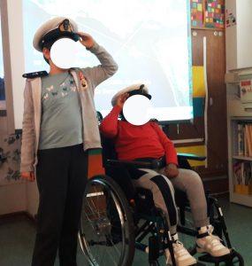 Dois alunos, um em pé e outro em cadeira de rodas, fazem a continência com os bonés na cabeça e as divisas colocadas nos ombros