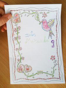 Um postal com desenhos pintados inspirados nos lenços dos namorados portugueses com o nome Inês