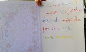 Versos escritos à mão, cada palavra a sua cor, dedicados à mãe: minha mãe é uma flor, a maior deste jardim, obrigada mãezinha por teres sido sempre assim
