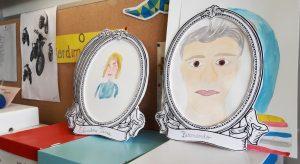 Parede da sala da escola com dois retratos a aguarela emoldurados