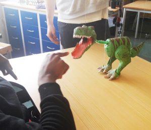 Um dinossauro marioneta é manipulado pelo Pedro e uma aluna estica o dedo em direção à boca do bicho que está aberta de forma feroz