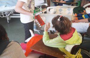 Outra marioneta manipulada pelo Pedro com uma grande dentadura abre a boca em direção a uma aluna