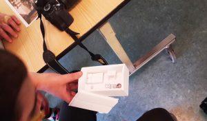 Uma caixa pequena da maqueta com miniaturas de uma cama, mesa, fogão que simulam a casa de um faroleiro