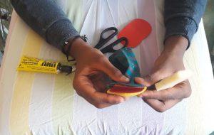 As mão de um aluno em maca a construir o seu fantoche a partir de uma meia com cola, tesouracartolinas e esponja.