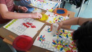 Um aluno e pos seus pais trabalham em conjunto em folhas de papel aguarela e carimbos artesanais.
