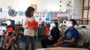 Eugénia mostra o peixe em espuma cor de laranja aos alunos.