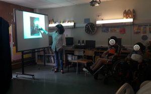 Eugénia aponta para a imagem da família do rei D. Luís projetada no quadro interativo e os alunos escutam atentamente.