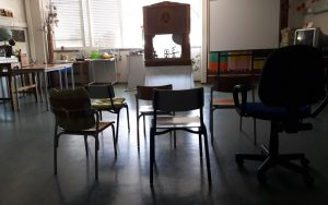 A sala com cadeiras vazias e o teatro de madeira com as sombras ao fundo, antes de começar.