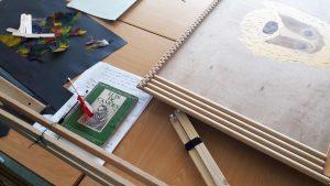 Numa mesa encontram-se pedaços de cartolina e de papel celofane, madeiras e um livro de Luís de Camões.