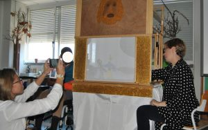 A professora e um aluno manipulam as marionetas e outra professora fotografa o espetáculo.