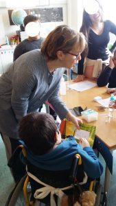 Um aluno em cadeira de rodas faz a experiência da escrita mágica sob orientação da professora.