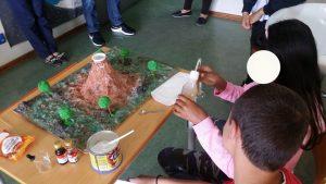 Dois alunos de Alcabideche elaboram a experiência do vulcão em erupção.