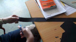 Um aluno corta cartolina preta para fazer os cenários.
