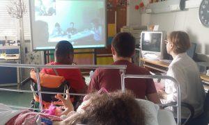 Dois alunos sentados e uma aluna na cama com a professora olham para o quadro onde se encontra a imagem dos alunos e professoras do HDE.