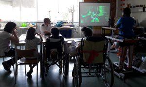 Um grupo de alunos, uma mãe e o faroleiro Santa Neto olham para o quadro onde o filme decorre.