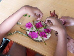 As mãos de uma aluna a construir uma mandala com flores, bagas e folhas.
