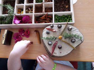 As mãos de um aluno a construir uma mandala com flores, frutos e folhas.