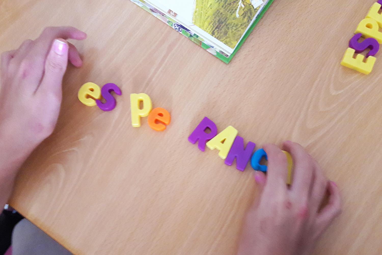 Aluna a tentar compor a palavra esperança com letras magnéticas.
