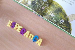 Um detalhe do livro aberto e a palavra ESPERANÇA com letras magnéticas sobre uma secretária.