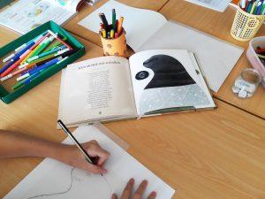 Aluna desenha a foca-monge-das-Caraíbas a partir da ilustração da autora do livro