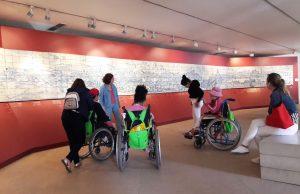 Alunos em cadeiras de rodas e em pé com a gui do museu observam o painel de azulejos da cidade de Lisboa