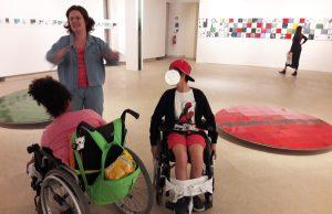 Dois alunos em cadeira de rodas e a guia do Museu a falar sobre as obras de Haru Ishii.
