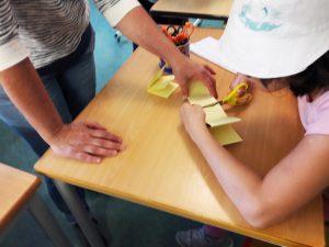 Uma aluna corta uma tira de papel dobrada como um harmónio com a ajuda de uma das mediadoras culturais.