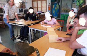 Um grupo de alunos dispostos em mesa redonda a escutar a mediadora cultural e a observar uma revista de Almada Negreiros.