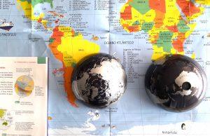 Um mapa mundo e um globo terrestre dividido ao meio em cima de uma secretária.