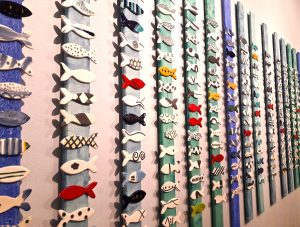 Várias tiras verticais com peixes de cores e motivos diferentes alinhados em arte de azulejo.