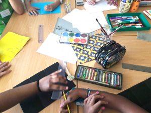 Mãos dos alunos a tirar as medidas sobre papel de cartolina.