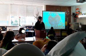 <na sala da escola os alunos, à volta de uma mesa e um aluno em cama, observam uma ilustração antiga com uma ovelha e a mediadora cultural fala para os participantes.