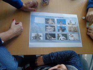 Alunos à volta da mesa com imagens dos deuses e heróis gregos