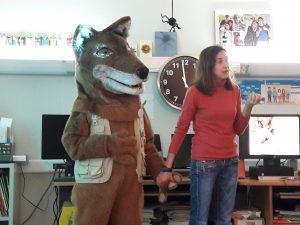 A bióloga de mão dada com a mascote fala para os alunos.