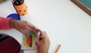 As mãos de uma aluna a desenhar um emoji sorridente numa cartolina quadrada.