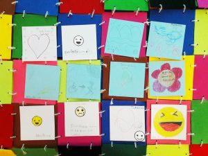 O conjunto dos retalhos feitos pelos alunos sobre a manta de retalhos colorida.