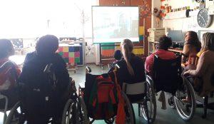 A sala de aula com uma imagem projetada no quadro interativo e alunos a observarem a mediadora cultural a falar.