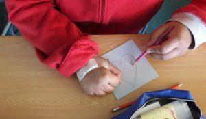 As mãos de uma aluna a desenhar um coração numa cartolina quadrada.