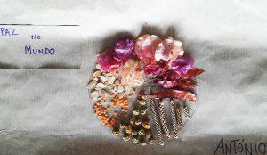 Uma mandala feita com folhas e frutos secos, flores e lentilhas intitulada A Paz no Mundo