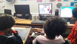 Os alunos observam o monitor do computador onde se encontram os colegas da outra escola a falar.