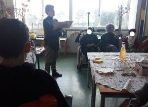 A professora lê a história para os alunos e familiares.