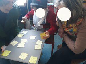 Um aluno joga o jogo feito com pequenos cartões amarelos e com imagens para fazer uma abraço.