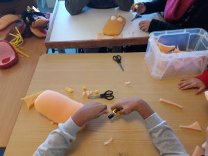 As mãos de aluna a colar marioneta de espuma