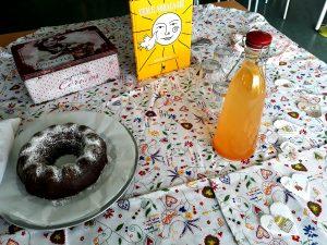 A mesa com toalha dos lenços dos namorados, garrafa, bolo de chocolate, caixa com bolachas e o livro Vem e abraça-me.